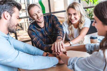 happy young business team stacking hands at workplace