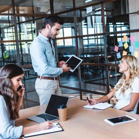 Photo pour Jeune homme d'affaires utilisant une tablette numérique et regardant sourire collègue femme sur le lieu de travail - image libre de droit