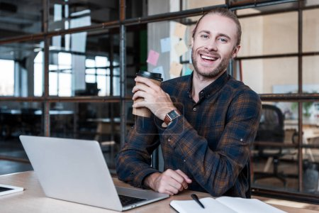 handsome young businessman holding paper cup and smiling at camera while working with laptop in office