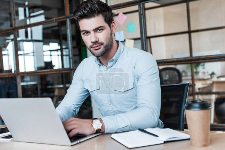 handsome young businessman using laptop and looking at camera at workplace