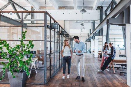 Photo pour Souriant jeunes collègues d'affaires en utilisant une tablette numérique et de parler tout en marchant sur l'espace de travail - image libre de droit