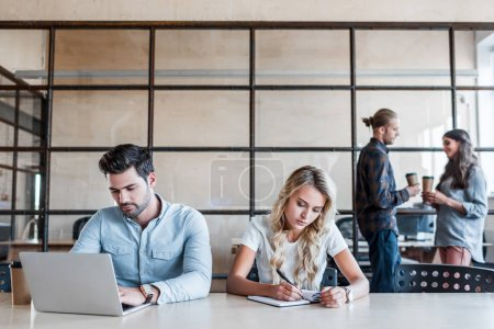 young business people working at workplace while colleagues drinking coffee behind