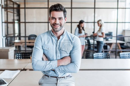 Photo for Handsome young businessman with crossed arms smiling at camera in office - Royalty Free Image