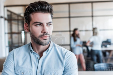 portrait of handsome pensive young businessman looking away in office