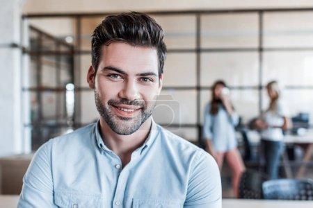 Photo pour Portrait de beau jeune homme d'affaires souriant à la caméra dans le bureau - image libre de droit