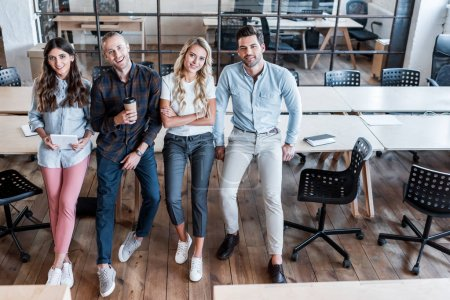 Photo for High angle view of four young business colleagues sitting on tables and smiling at camera in office - Royalty Free Image