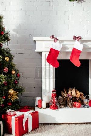 Photo pour Arbre de Noël avec des boules, boîtes-cadeaux et cheminée avec bas de Noël à la maison - image libre de droit