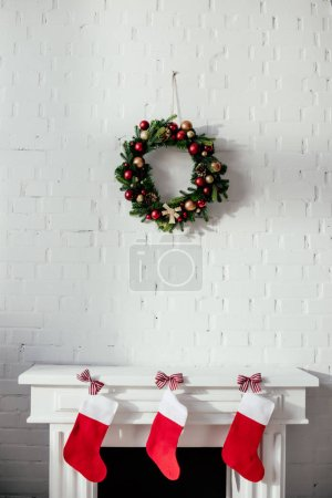 fireplace with christmas stockings and fir wreath with baubles hanging on brick wall in room
