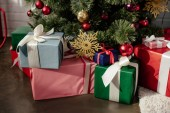 colorful presents under christmas tree with baubles in room
