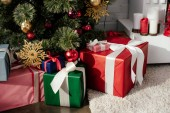 gift boxes under christmas tree with baubles in room