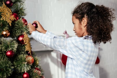 side view of adorable african american child in pajamas decorating christmas tree with baubles at home