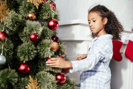 adorable african american child in pajamas decorating christmas tree with red toys at home