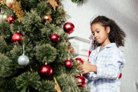 adorable african american child in pajamas decorating christmas tree with red balls at home