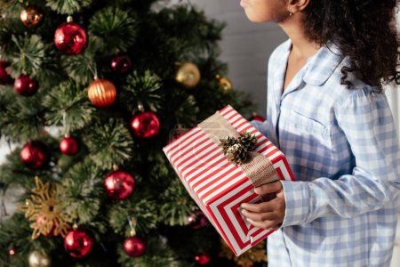 cropped image of african american child in pajamas holding christmas gift box at home