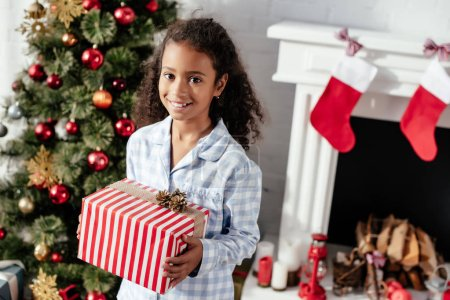 smiling adorable african american child in pajamas holding christmas present and looking at camera at home
