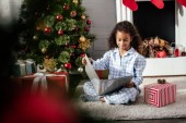 selective focus of adorable african american child in pajamas reading book near christmas tree at home