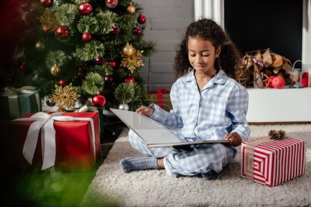 Photo for Cheerful adorable african american child in pajamas reading book near christmas tree at home - Royalty Free Image