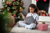 adorable african american child in pajamas reading book near christmas tree at home