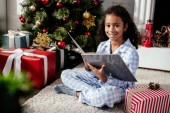 smiling adorable african american child in pajamas holding book near christmas tree and looking at camera at home