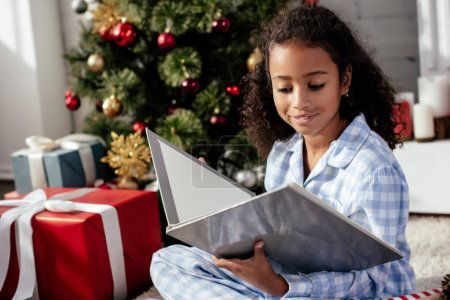 cheerful adorable african american child in pajamas reading book near christmas tree at home