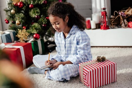 Photo for Adorable african american child in pajamas writing something to copybook at home, christmas concept - Royalty Free Image