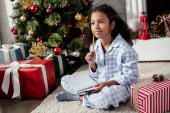 adorable pensive african american child in pajamas sitting with copybook near christmas tree at home