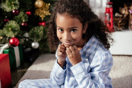 adorable african american child in pajamas sitting on floor and looking at camera near christmas tree at home