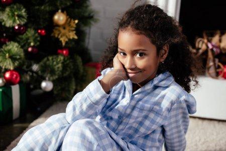 Foto de Adorable niño afroamericano en pijama sentada en el piso y mirando a cámara en casa, concepto de Navidad - Imagen libre de derechos