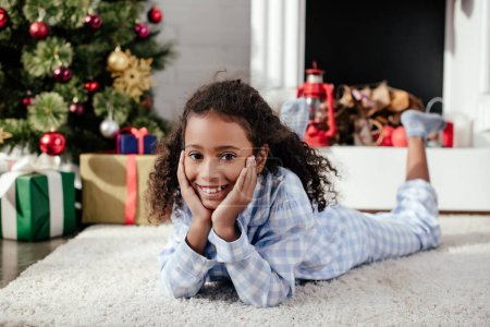 adorable african american child in pajamas lying on floor and looking at camera at home, christmas concept