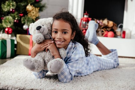 smiling adorable african american child in pajamas lying on floor with teddy bear at home, christmas concept