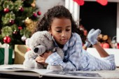 adorable african american child in pajamas with teddy bear looking at photo album on floor at home
