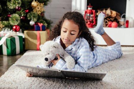 Photo pour Adorable enfant afro-américain en pyjama avec nounours, lecture de livre sur le plancher à la maison, le concept de Noël - image libre de droit