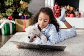 adorable african american child in pajamas with teddy bear reading book on floor at home, christmas concept