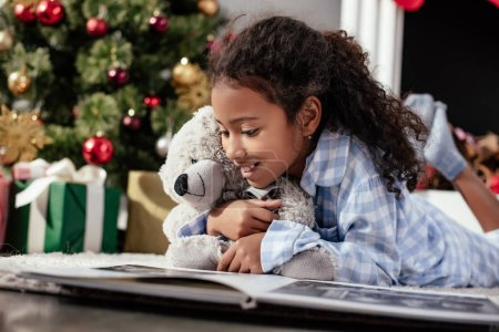 Photo for Happy adorable african american child in pajamas with teddy bear looking at photo album on floor at home - Royalty Free Image
