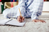 cropped image of african american child in pajamas writing something in notebook with pencil at home