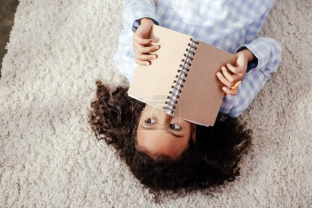elevated view of adorable african american child in pajamas lying on carpet and covering face with copybook in room