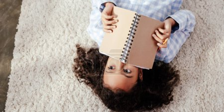 Photo for Top view of adorable african american child in pajamas lying on carpet and covering face with copybook in room - Royalty Free Image