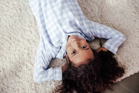 top view of smiling adorable african american child in pajamas lying on carpet in room