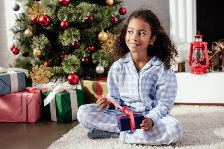 Photo pour Heureuse enfant afro-américain adorable en pyjama ouverture de cadeau de Noël à la maison et à la recherche de suite - image libre de droit