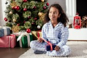 happy adorable african american child in pajamas opening christmas gift at home and looking away