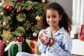 smiling adorable african american child in pajamas holding christmas gift and looking at camera at home