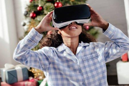 Photo pour Enfant afro-américain en pyjama avec casque de réalité virtuelle à la maison, le concept de Noël - image libre de droit