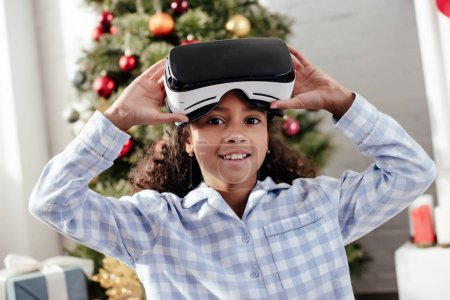 Photo for African american child in pajamas using virtual reality headset and looking at camera at home, christmas concept - Royalty Free Image