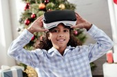 african american child in pajamas using virtual reality headset and looking at camera at home, christmas concept