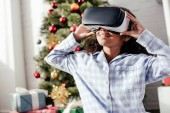 cheerful african american child in pajamas using virtual reality headset at home, christmas concept