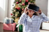 happy african american child in pajamas using virtual reality headset at home, christmas concept