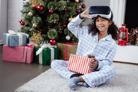 Photo for African american child in pajamas and virtual reality headset sticking tongue out and winking at home, christmas concept - Royalty Free Image