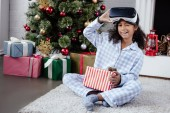 niño afroamericano en pijamas y casco de realidad virtual pegándose la lengüeta hacia fuera y guiñando un ojo en el hogar, concepto de Navidad