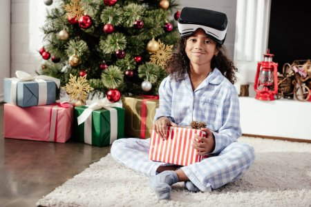 Photo for Smiling african american child in pajamas and virtual reality headset holding present at home, christmas concept - Royalty Free Image