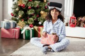 smiling african american child in pajamas and virtual reality headset holding present at home, christmas concept